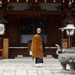 Buddhist monk in front of temple in Kyoto, Japan